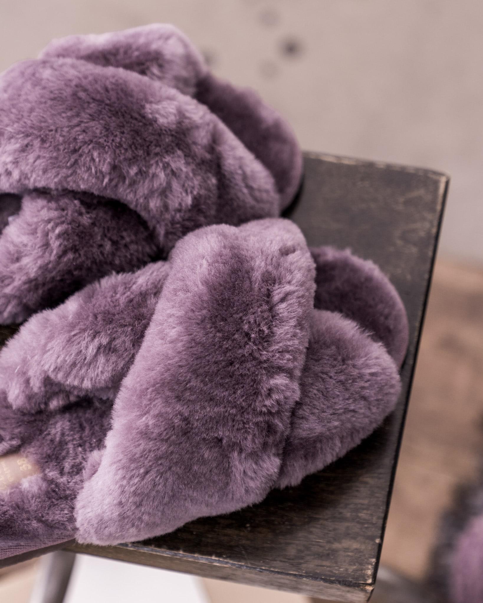 Ett par mjuka fårskinnstofflor i en trendig slip-in modell. Tofflorna ha en bred omlottlagd ovandel med öppen tå. Kantband i textil runt sulan. Yttersula i EVA vilket gör att den med fördel även kan användas utomhus.