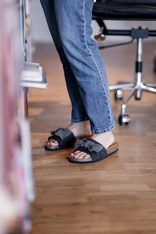 Ett par slip-in sandaler med öppen tå. Sandalerna har en stor dekorativ rosett fram. Fotformad sula i kork klädd med mocka vilket gör att sandalen andas på ett naturligt sätt. Yttersula i EVA för låg vikt och stötdämpning.